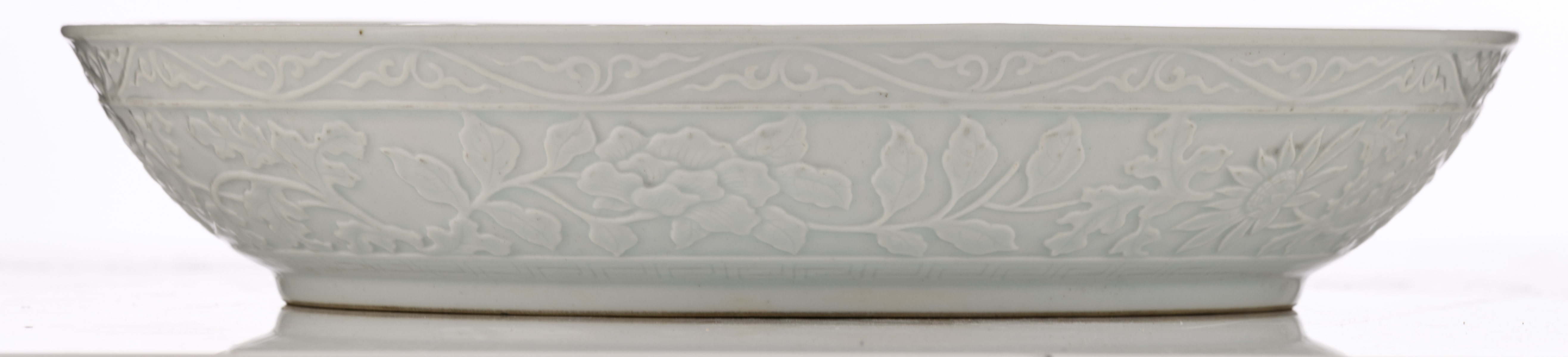 Lot 28 - A Chinese floral relief decorated white glazed charger, the well with a lotus bouquet, H 7 - ø 35,