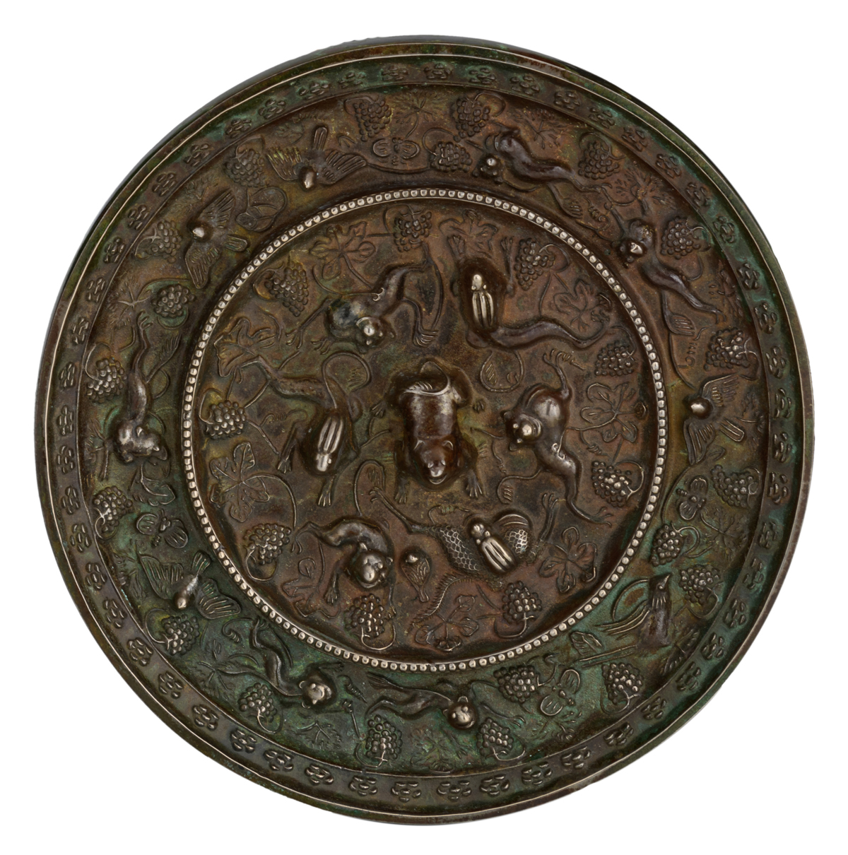 Lot 12 - A Chinese silver plated bronze circular mirror, decorated with animals amidst fruiting grapevine,