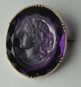 BROSCHE oval, Frauenportrait in lila Stein, welcher rückseitig facettiert ist, vergoldete Fassung