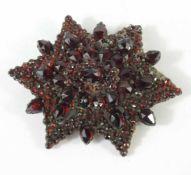 Granat- Brosche, Böhmen um 1900breite Sternform, 4*4,4cm, ca.2 Steine zu ergänzen