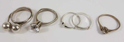4 silberne Ringe und ein Ring, 333er Gold, Silber-Gew.10,71g, unterschiedliche Arten und Größen, U.
