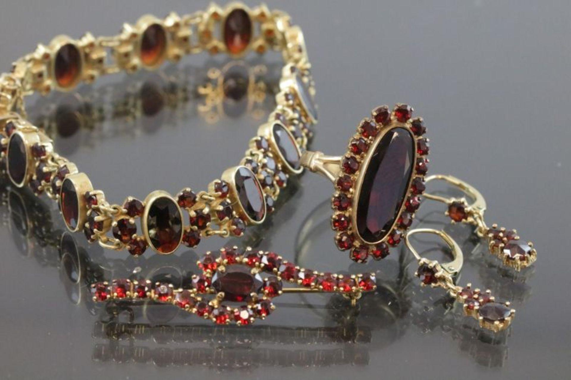 Los 26 - Granat-Set, 333 Gold/Metall28,5 Gramm Set bestehend aus Armband, Brosche, Ring und Ohrsteckern.