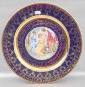 Tellerrund, kobaltblau, gold verziert, Spiegel mit Darstellung der drei Grazien verziert, Dm 25 cm