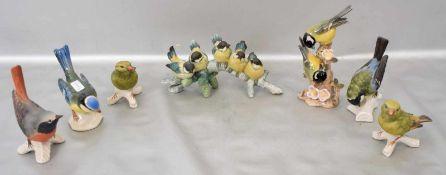 Konvolut sieben Vögelauf Ast sitzend, bunt bemalt, verschiedene Ausführungen, teilweise FM Goebel