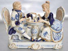 FigurenpaarElegantes Paar am Tisch sitzend, auf rechteckigem Sockel, blau/gold bemalt, H 21 cm, B 27