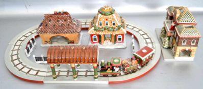 Eisenbahnmit Schienen, drei Häusern, Bahnhof und Zubehör, mit Weihnachtsmotiven verziert, bunt