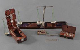 2 antike Goldwaagen, 1 Gewichtssatz und 1 Diamanten Lehre2 Goldwaagen im Holzkasten mit