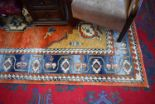 Lot 6 - A Middle Eastern style woollen carpet, in tones of blue, red and cream,