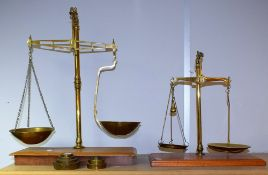 A set of 20th century balance scales, brass on wooden base, approx 60cm high; another similar,