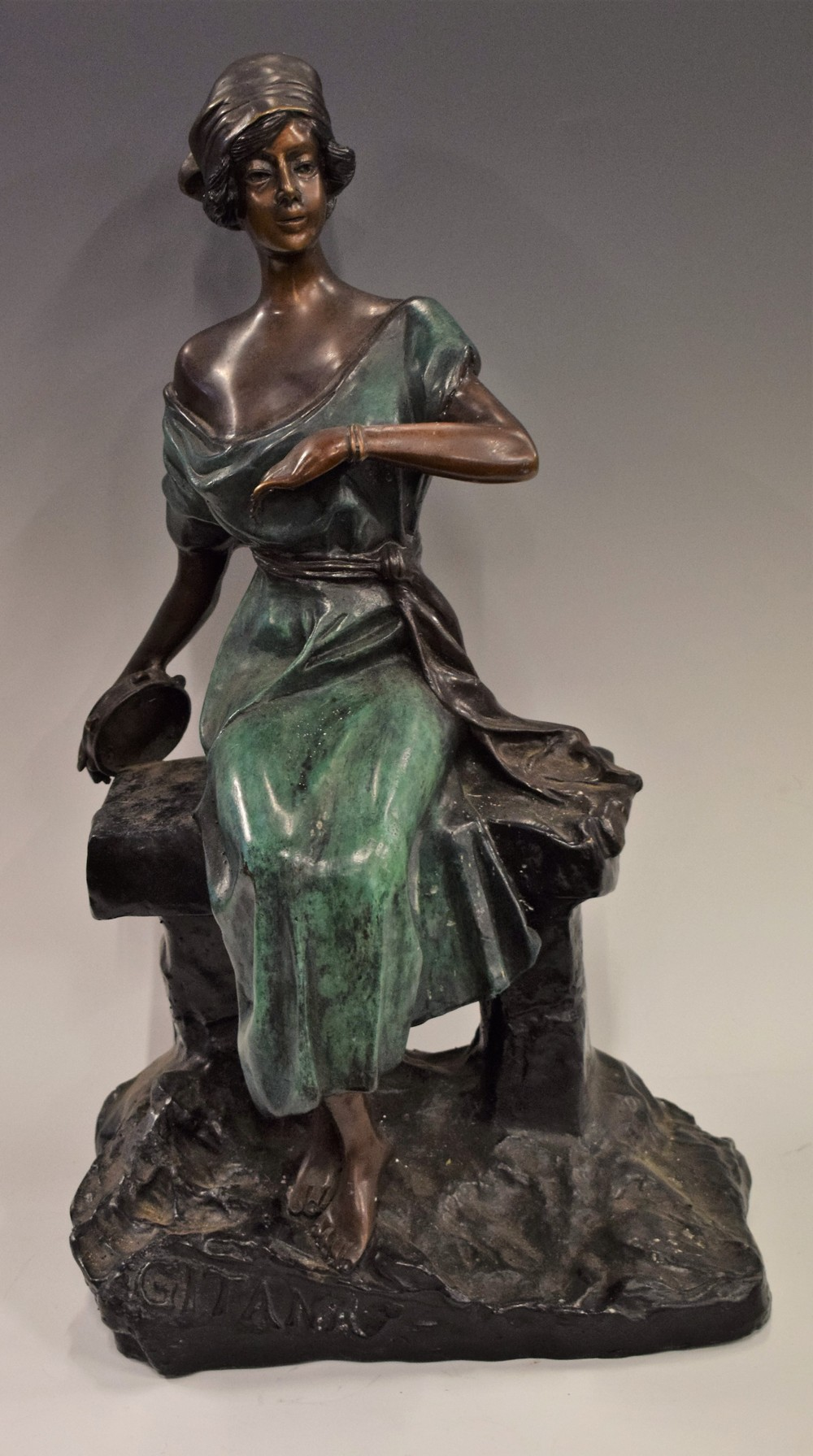 Lot 45 - Gitana, after, a reproduction bronze figure, seated Art Deco style girl, holding a tambourine,