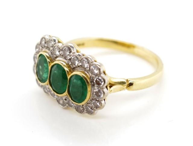 Lot 25 - Emerald trilogy and diamond halo ring