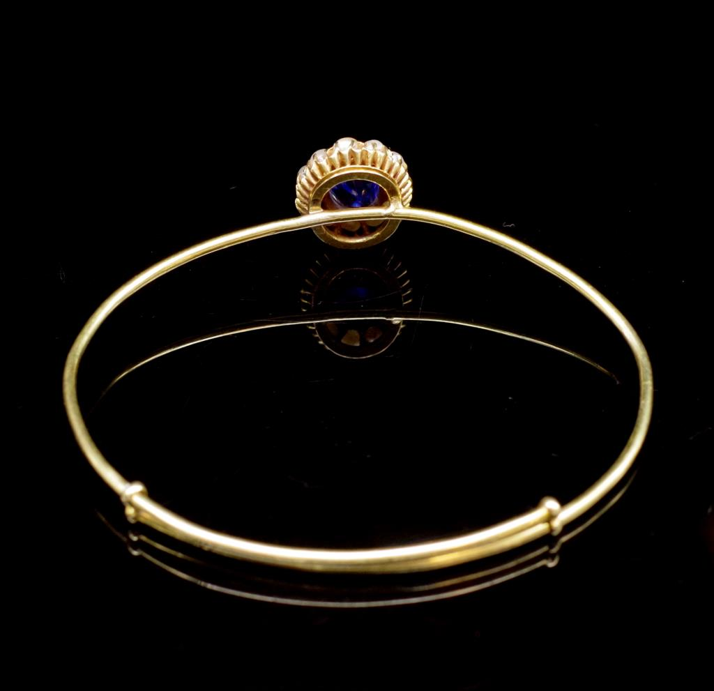 Lot 57 - 3.00ct Blue sapphire, seed pearl set gold bangle