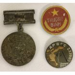 2 Vietnam War Era N.V.A/Vietcong badges and a medal found in a street market in Saigon.