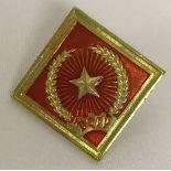 Vietnam War Era D.Q.T.V helmet badge in red and gold.