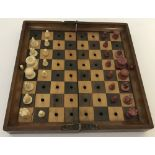 An Antique hinged travelling wooden chess board with red and white ivory chess pieces by Jaques.