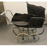 A vintage Silver Cross dolls pram in brown and cream colourway.