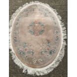 An oval Chinese wool rung with fringed ends.