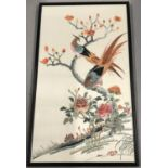 A framed and glazed embroidered silk panel of oriental pheasants in a tree.