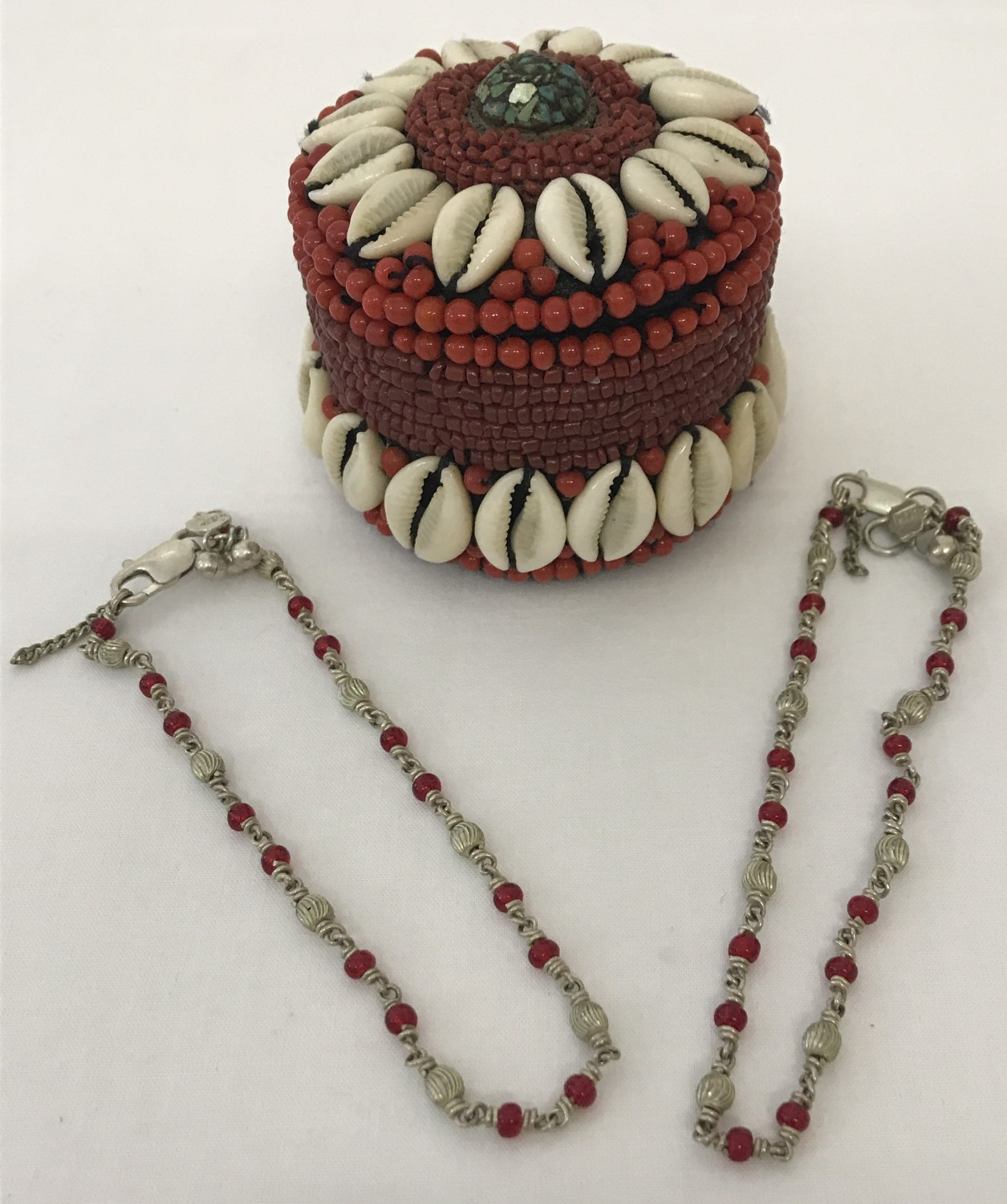 Lot 10 - 2 Indian white metal and red glass bead decorative ankle chains, both with makers marks.