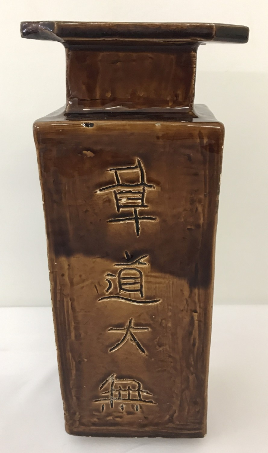 Lot 52 - A Chinese brown glaze 4 footed square shaped vase. Chinese script to each side.