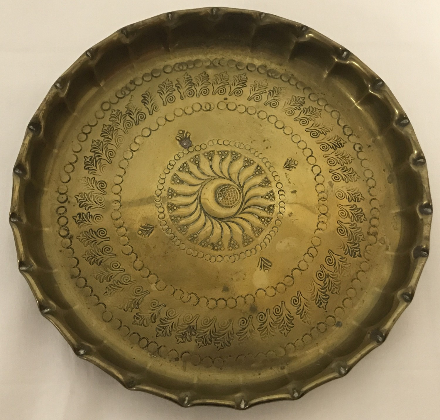 Lot 26 - A brass circular dish with hammered Persian decoration to interior and shaped rim.