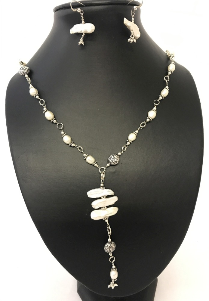 Lot 98 - A matching necklace and earrings set made with natural blister & freshwater pearls and floral beads.