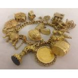 An 18ct gold charm bracelet with lobster clasp, safety chain and 14 charms of mixed ct gold.