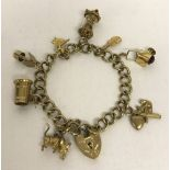 A 9ct gold charm bracelet with decorative padlock, safety chain and 8 charms.