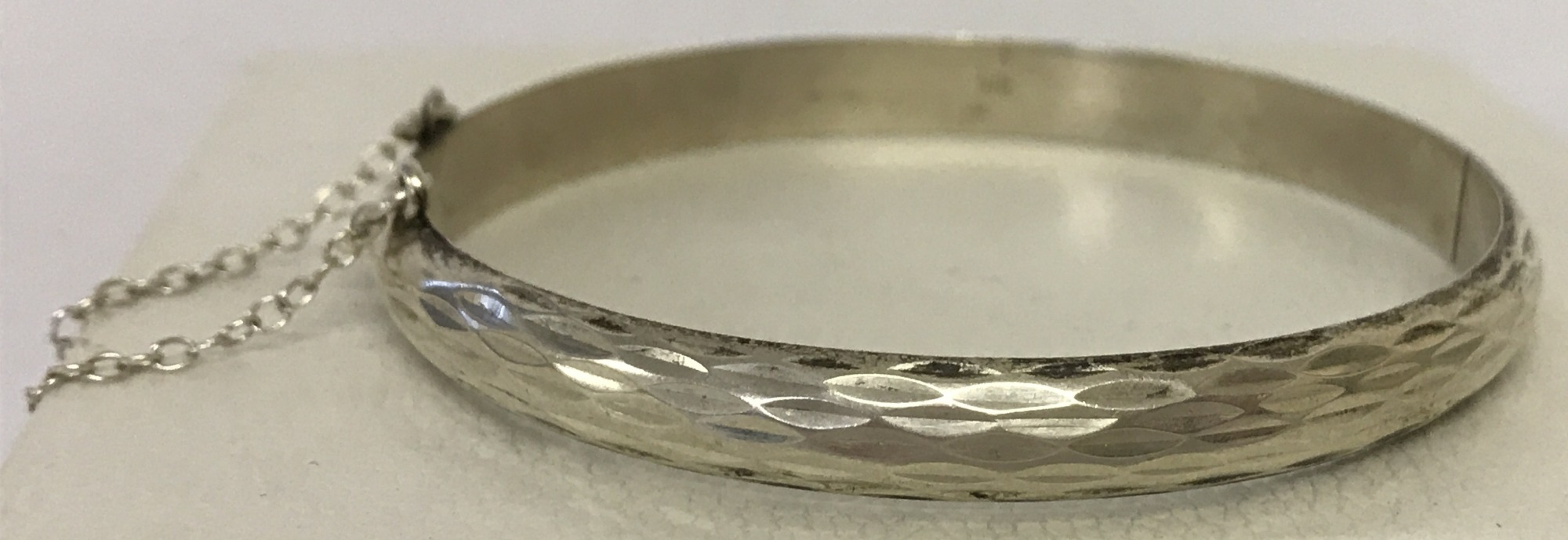 Lot 40 - A vintage silver hinged bangle with engine turned decoration and safety chain.
