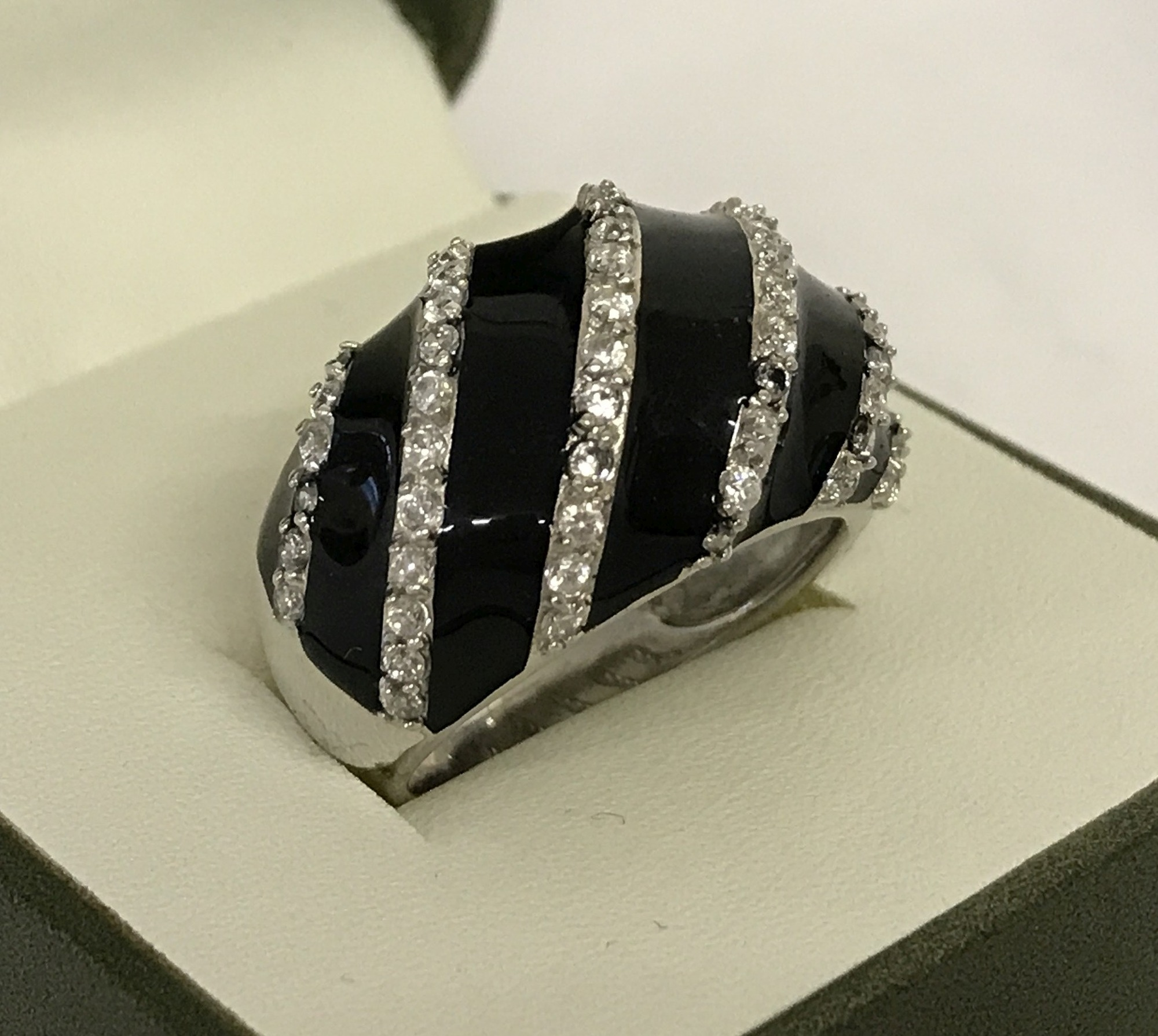 Lot 31 - A ladies black enamel and clear stone set dome style dress ring.
