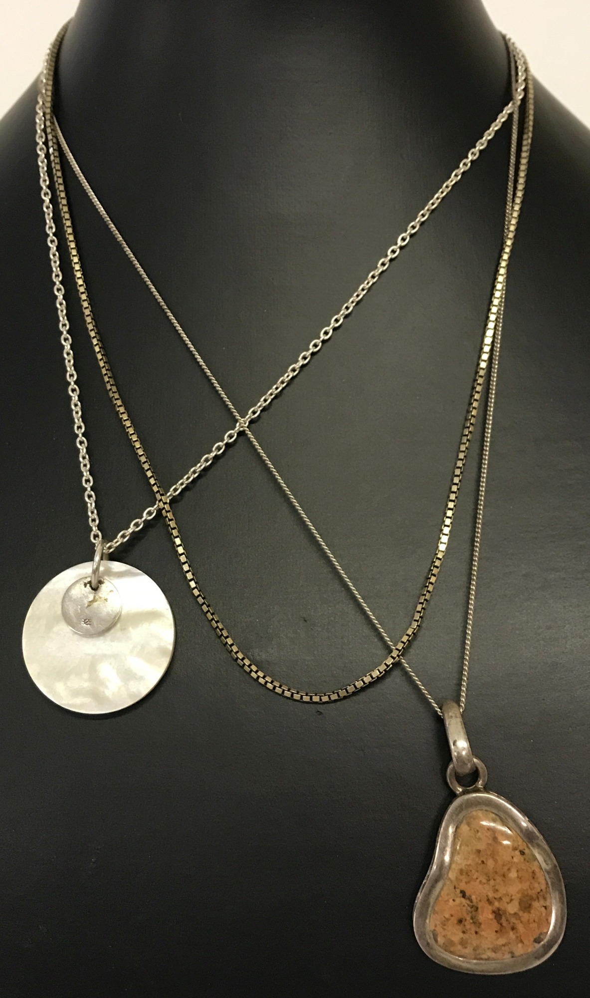 Lot 28 - A modern design natural stone set pendant on a fine curb chain with extension.