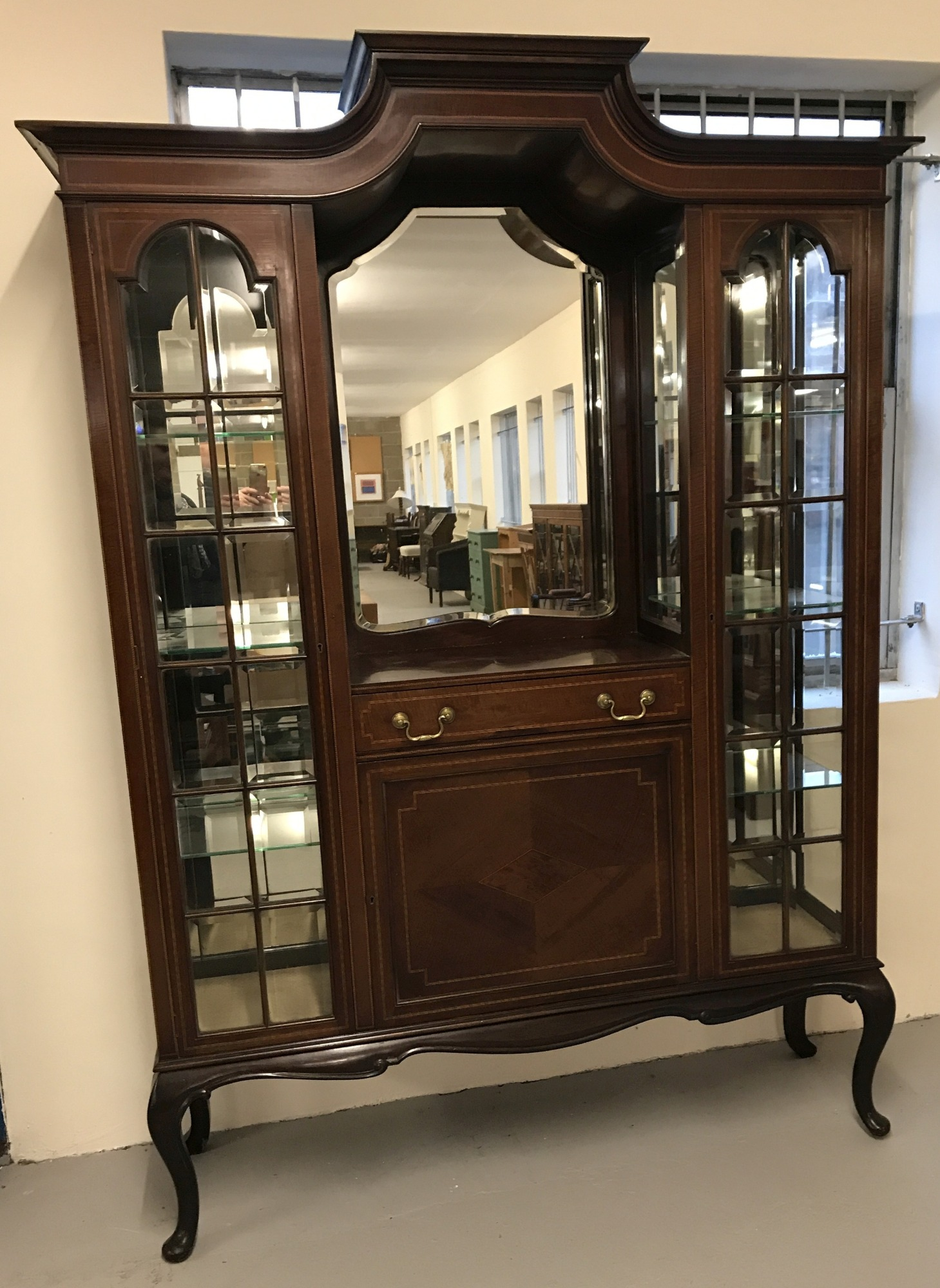 Lot 497 - A Victorian mirror backed glass fronted display cabinet with central cupboard and drawer.