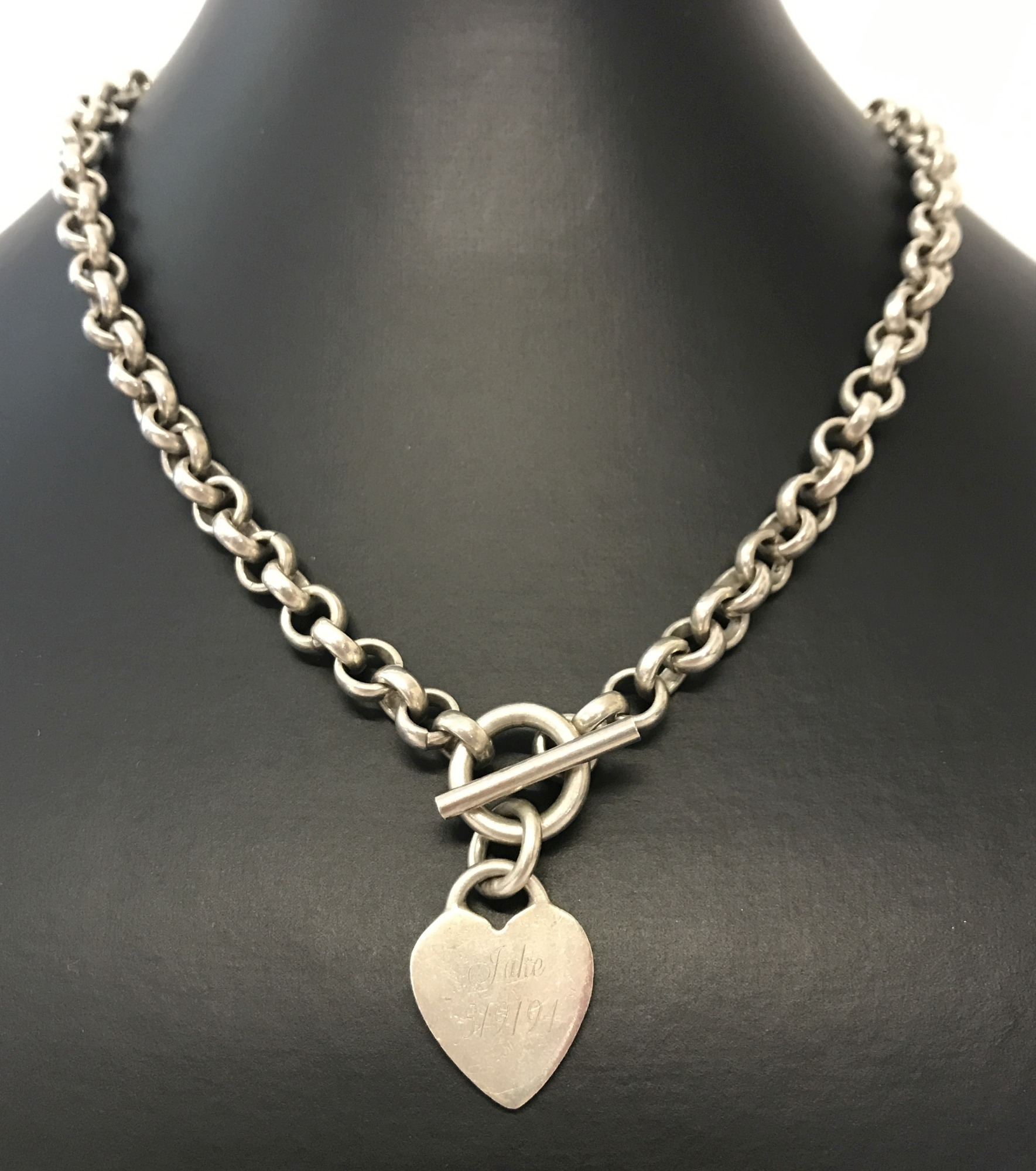 Lot 13 - A heavy belcher chain with front T bar fixing and dangle heart pendant.