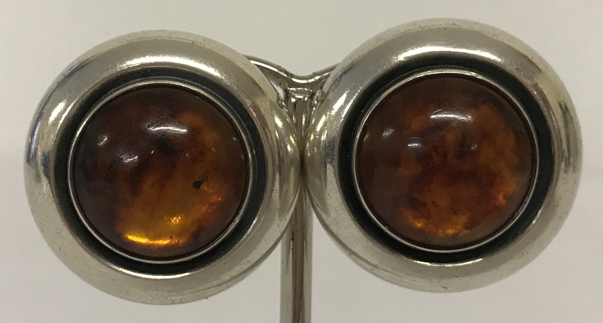 Lot 37 - A pair of vintage amber and Danish silver, circular clip on earrings by designer Niels Erik From.