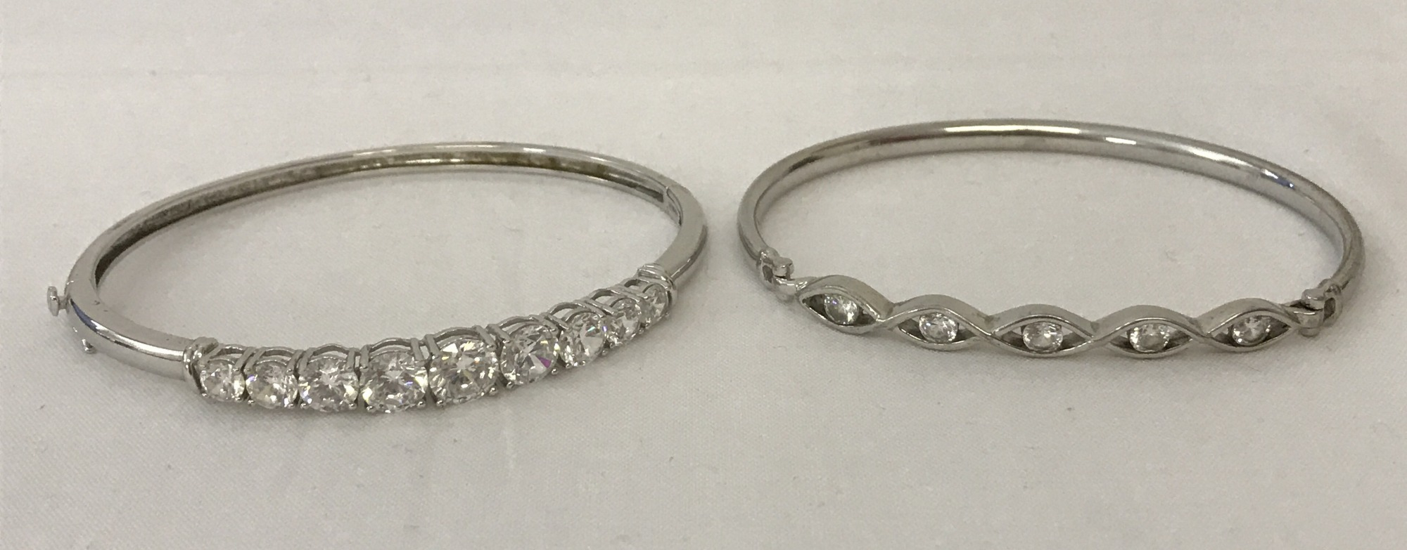 Lot 12 - 2 ladies silver bangles both set with cubic zirconia stones.