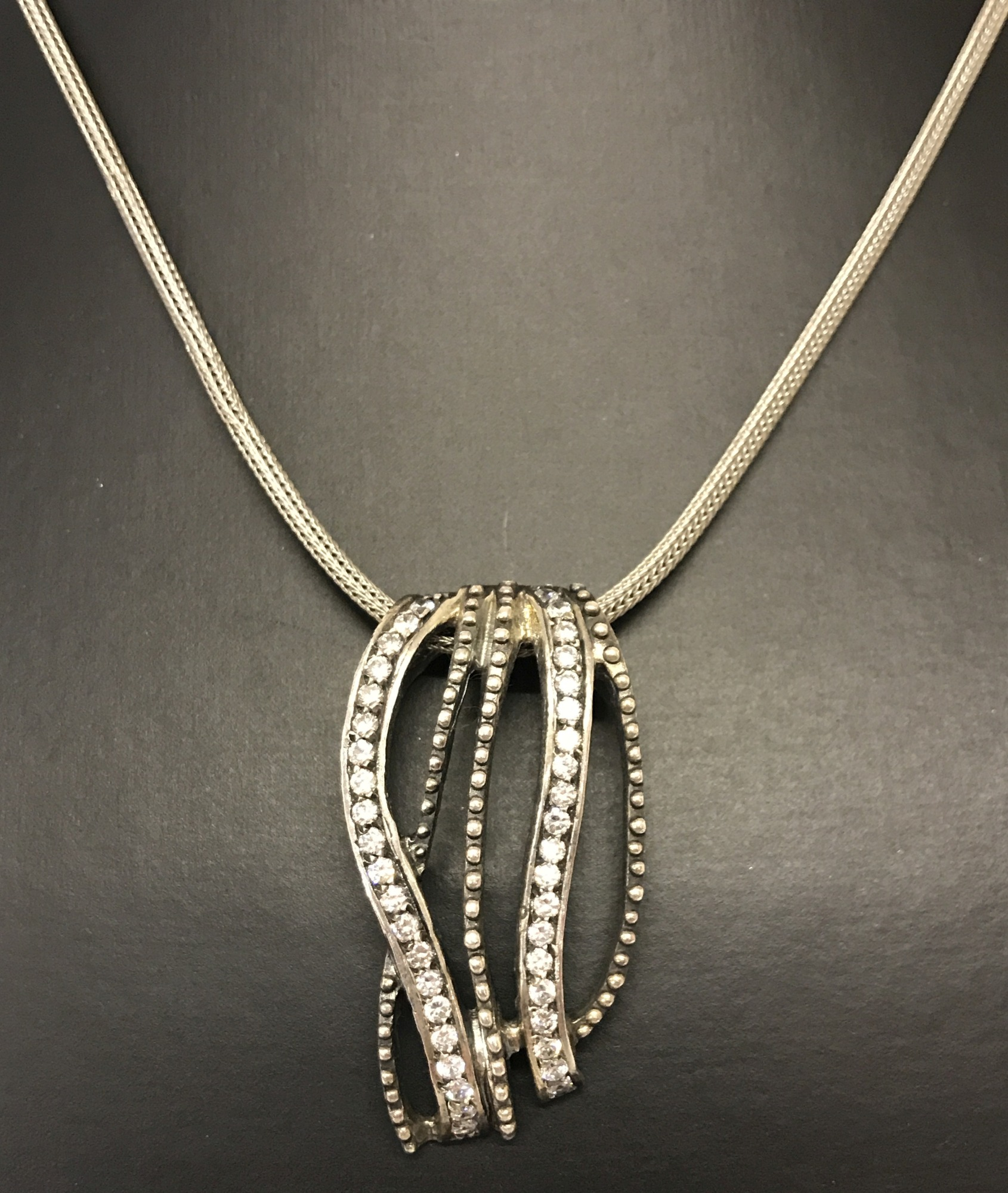 Lot 33 - A Portuguese contemporary silver pendant set with clear stones on a mesh style chain.