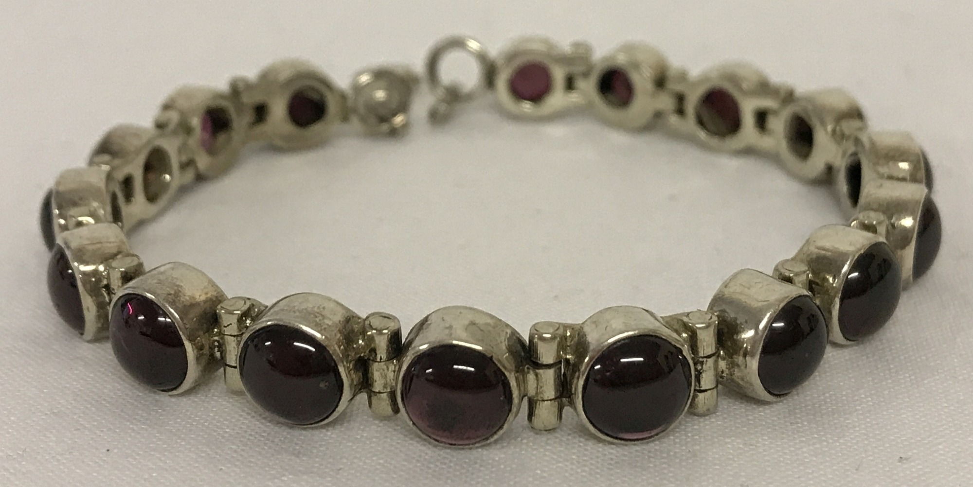 Lot 47 - A modern tennis style silver bracelet set with 17 garnet cabochon stones. With lobster clasp.