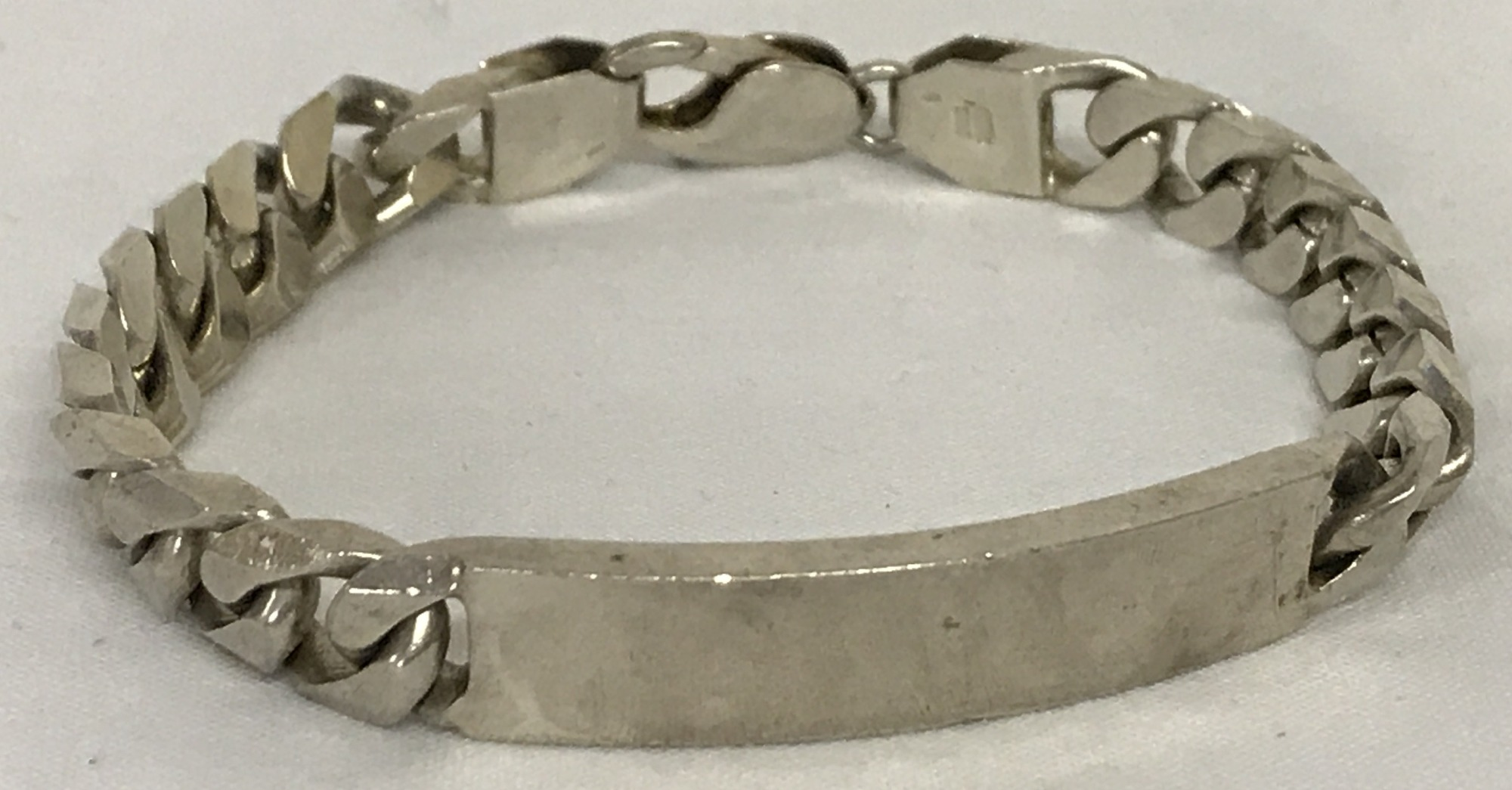 Lot 48 - A heavy silver curb chain identity bracelet.