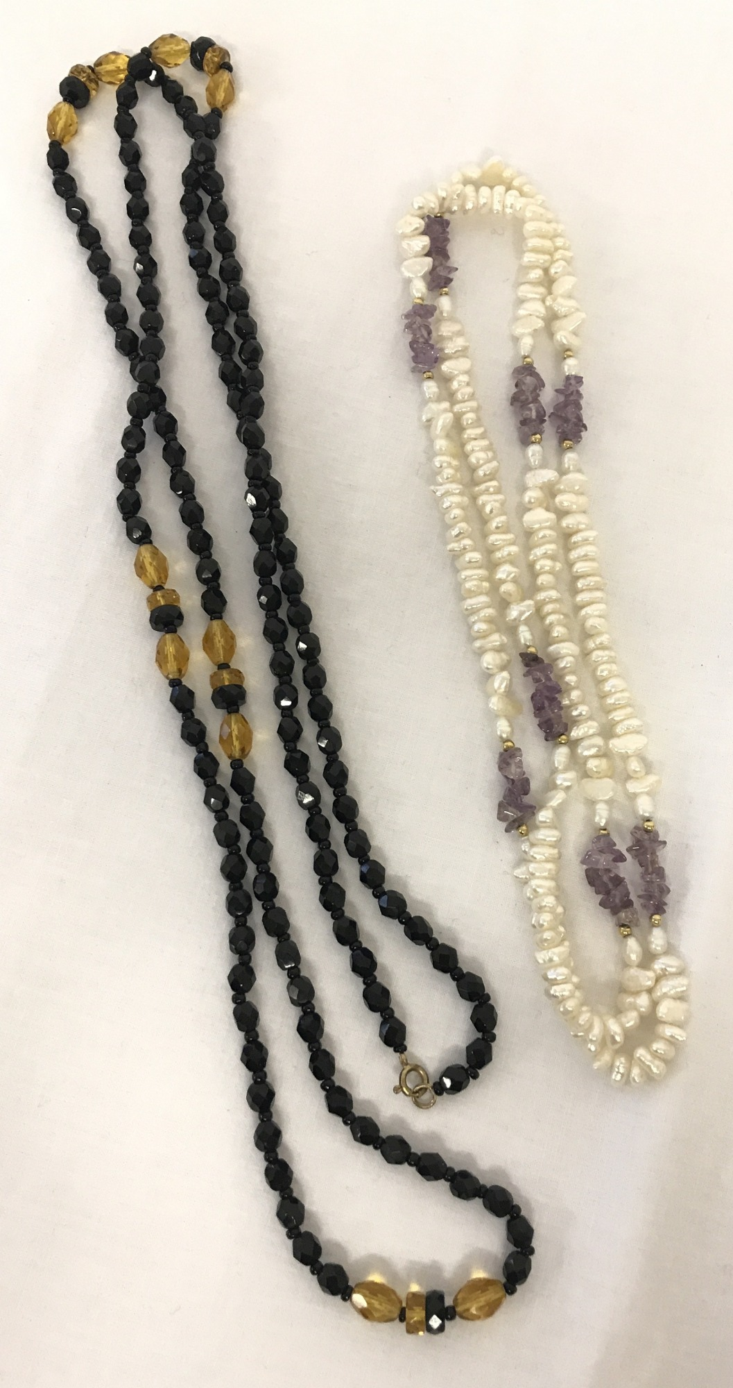 Lot 54 - 2 long, beaded neacklaces. A freshwater potato pearl and amethyst chip, long necklace.