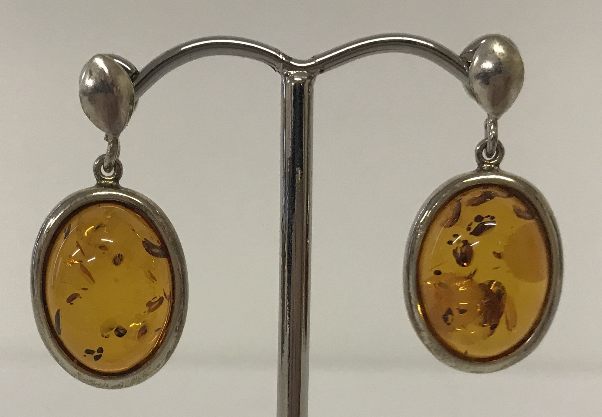 Lot 53 - A pair of oval white metal and Baltic amber drop earrings. Butterfly backs marked 925.