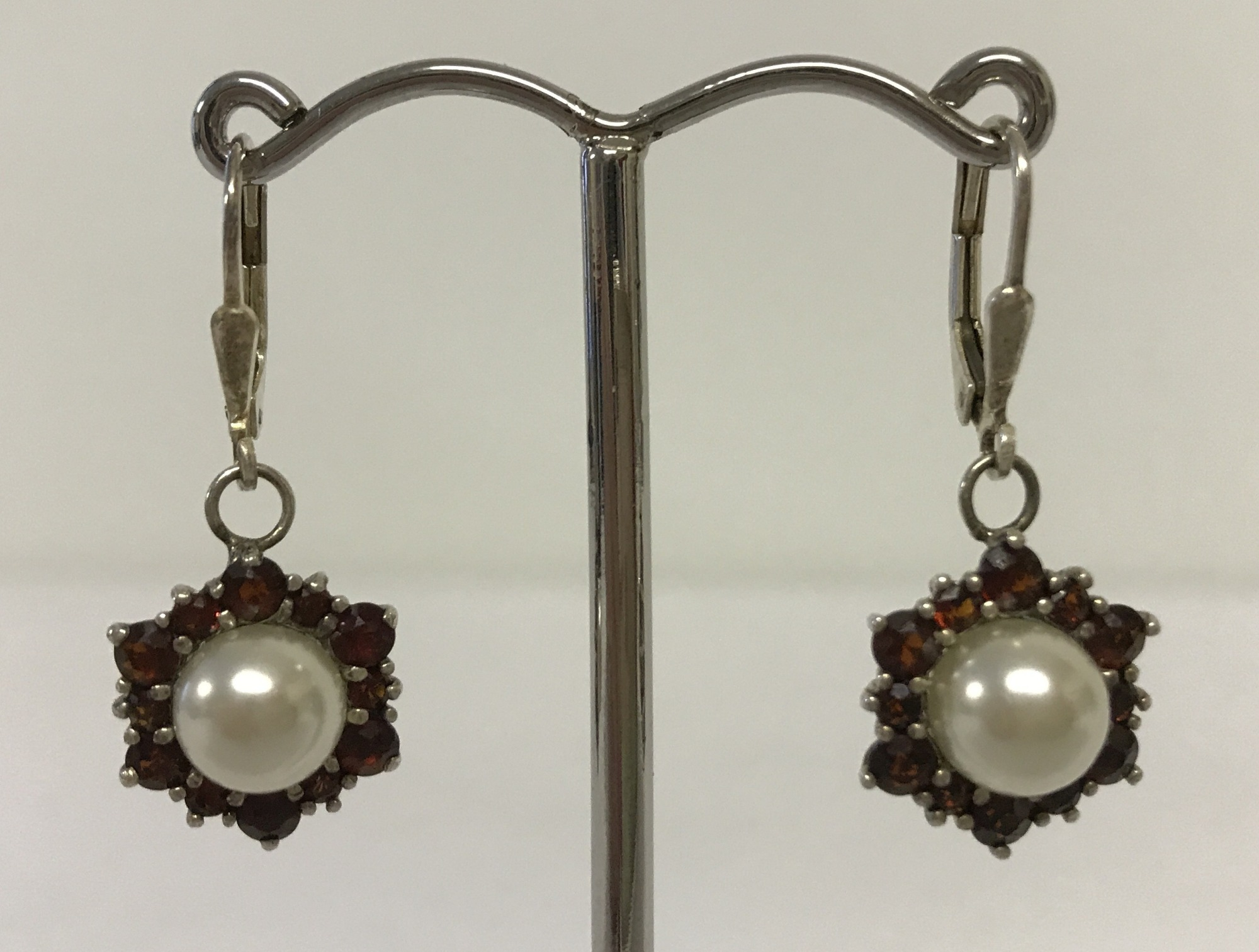 Lot 19 - A pair of faux pearl and garnet drop earrings.