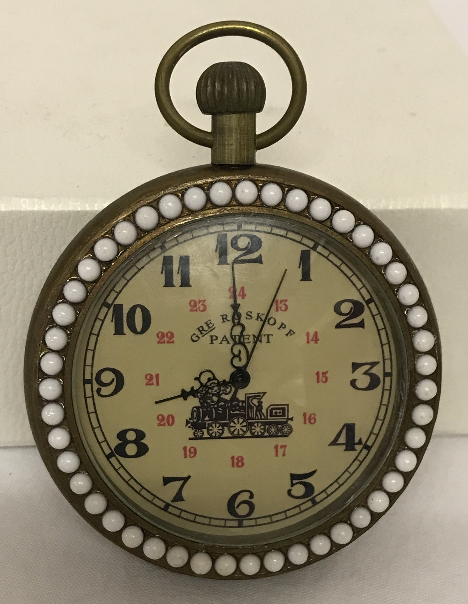 Lot 67 - A brass cased pocket watch with beaded detail to surround front and back.
