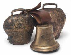 Drei KuhglockenDurchm.13, 14 bzw.16cm. Messing, mit Eisenklöppel.