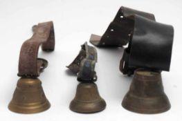 Drei Kuh- oder GeißenglockenMessing. Eisenklöppel. Durchm.8,5 bzw. 7,5 bzw. 10cm. Mit Lederbändern.