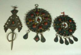 Drei div. Gewandspangen, orientalischRund bzw. fibelförmig, mit Korallen und farbigem Email besetzt.