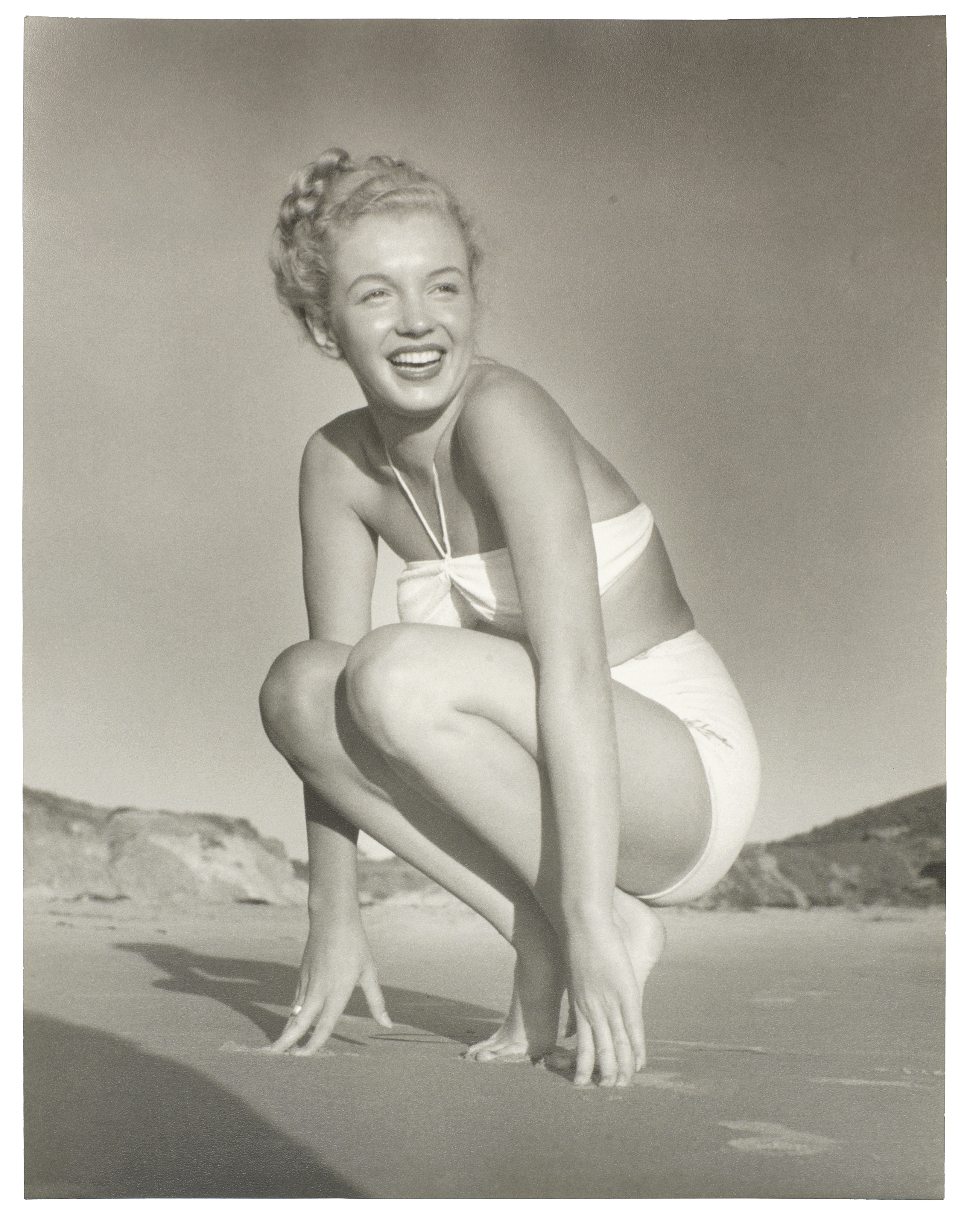 Lot 4 - ANDRE DE DIENES (ROMANIAN/AMERICAN, B.1913-D.1985): a black and white print of Marilyn Monroe on ...