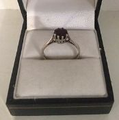 A Ladies Silver Dress Ring, Set with a single ruby coloured stone, ring size N1/2
