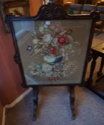 A William IV Rosewood Firescreen, With a floral decorated tapestry panel, raised on scroll