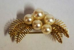 A 14ct Gold and Pearl Brooch, Set with seven cultured pearls on a gold leaf decorated mount, stamped