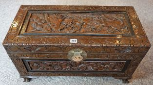 A Chinese Style Camphorwood Chest, The hinged top having a gilt metal lock, decorated with carved